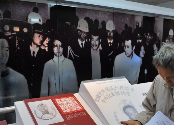 This photo taken on December 8, 2009 shows a visitor (R) reading documents in front of images showing Taiwan dissidents on trial in 1979, at the Jinmei Human Rights Park in Hsintien in Taipei county. Thirty years ago a group of Taiwanese opposition activists staged what was meant to be a peaceful human rights protest, but it proved to be a turning point in ending one-party rule on the island. The Kaohsiung demonstration on December 10, 1979, which unofficial estimates said involved between 10,000 and 30,000 people, was intended as a peaceful call for human rights, but dozens were injured when protesters clashed with police