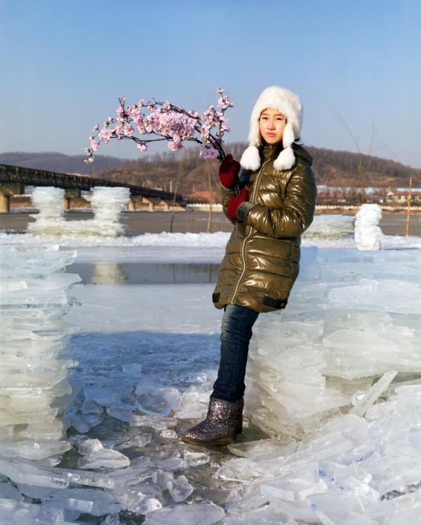 2018年2月,辽宁抚顺,10岁的于婷(音)站在浑河岸边,手里拿着一束用来装饰冰雕的人造花。
