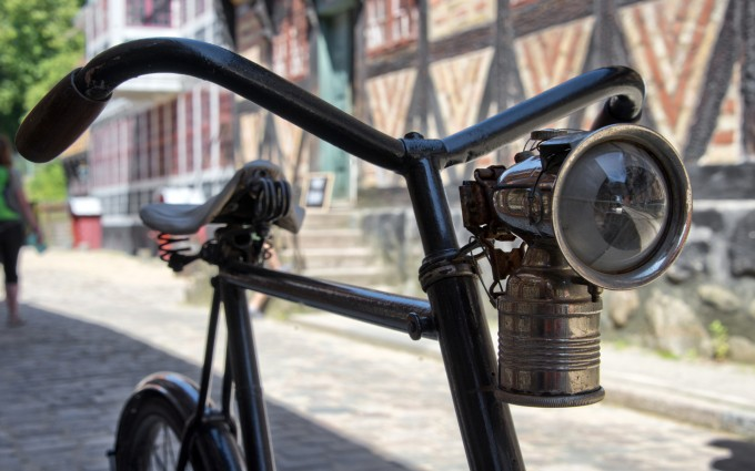 A vintage bicycle lamp is seen mounted on a bike.The main focus is on the front lens.