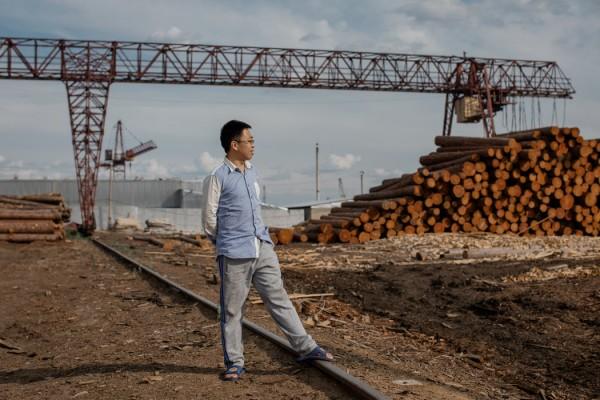中国贮木场工头王义仁(音)站在坎斯克的木料堆前,这些木材将装运到中国。
