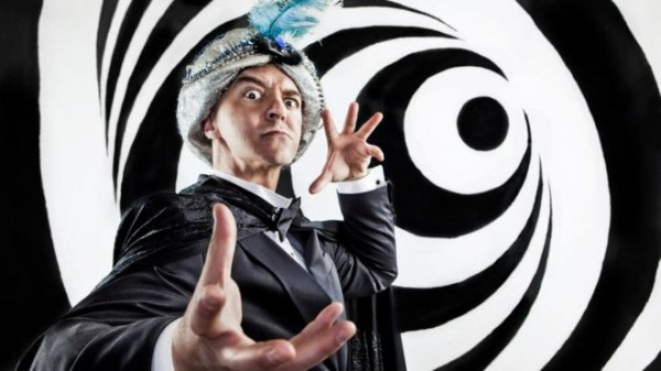 A man dressed as a magician performing a hypnotising trick