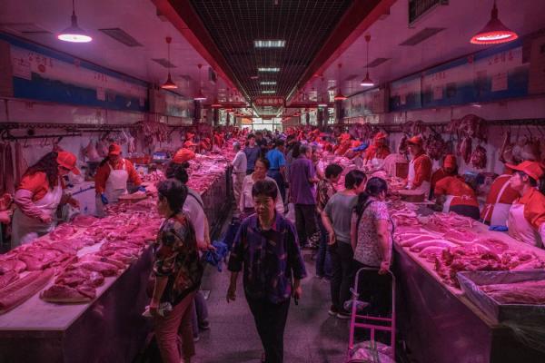 在北京一个肉类批发市场,顾客们在查看各种产品。