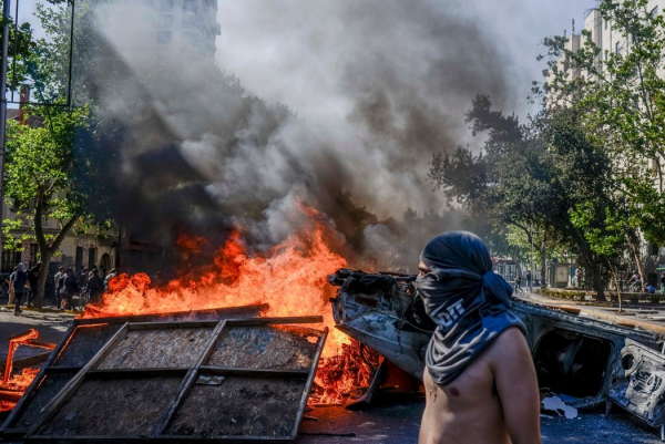 周二,智利圣地亚哥的抗议者。地铁票价上涨引发的示威演变成了致命的暴力事件。