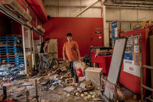在智利,人们从一家被抢劫的超市里翻出剩余的商品。