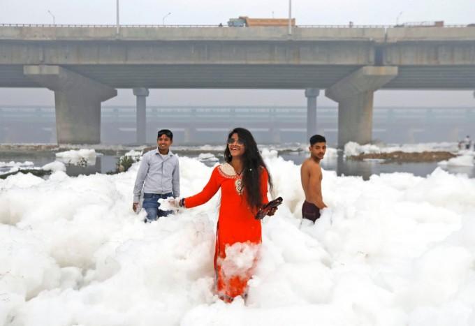 周日,人们在新德里受污染的亚穆纳河上拍照。河上的泡沫是由工业废料产生的。