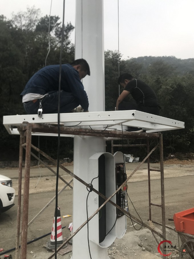 海光照明安装人员正在安装高杆灯灯盘
