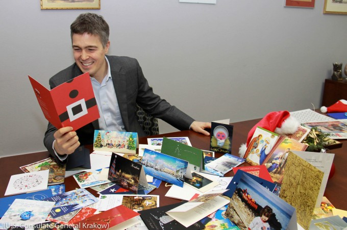 Man reading holiday cards at a desk (U.S. Consulate General Krakow)