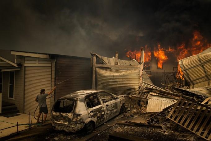 周二在澳大利亚康乔拉湖,一名男子试图与已经蔓延到邻居家的大火搏斗。