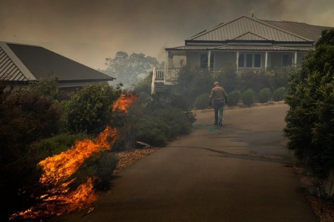 周二在新南威尔士州的渔夫天堂,一位居民在抢救他的房屋。